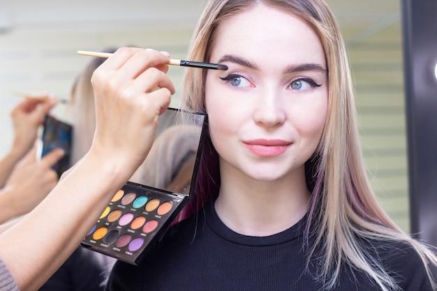 Visagist zet make-up op de ogen van het meisje. oogschaduw, palet. schoonheidssalon. detailopname