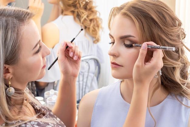 Visagist zet make-up op meisje model. huwelijksmake-up, avondmake-up, natuurlijke make-up. visagist zet oogschaduw op de oogleden.