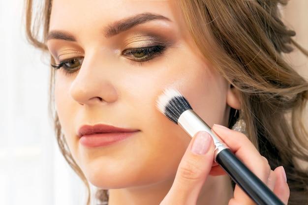 Visagist zet make-up op meisjesmodel. borstel poeder op jukbeenderen en gezicht.