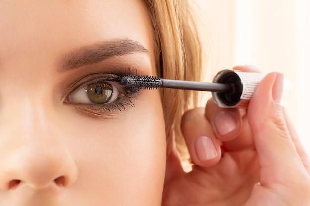 Visagist zet make-up op meisjesmodel. brengt mascara op wimpers aan