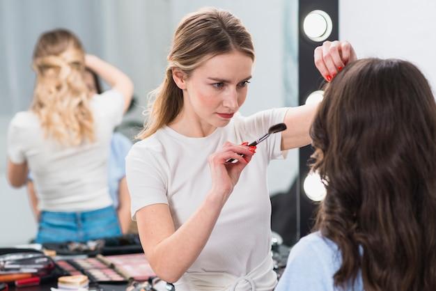 Visagiste die make-up voor jonge vrouw doet