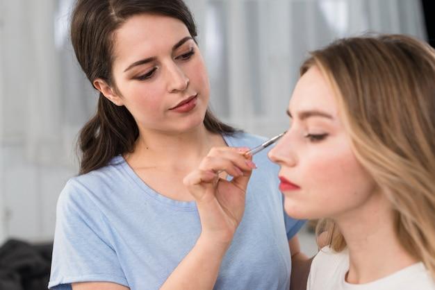 Visagiste doet make-up van ogen voor klant