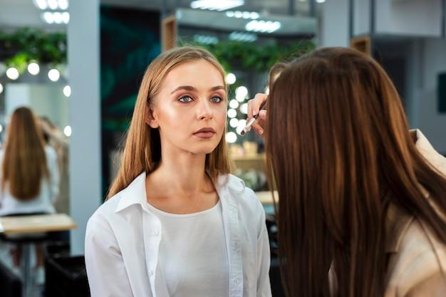 Visagiste doet make-up voor de vrouw
