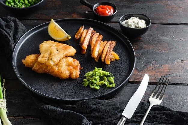 Vischips met dip en citroenzwart bord met brits traditioneel cusinevoedsel
