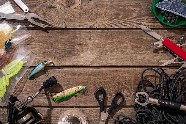 Visgerei - visserij spinnen, vislijn, haken en kunstaas op houten achtergrond. bovenaanzicht. kopieer ruimte. stilleven plat leggen