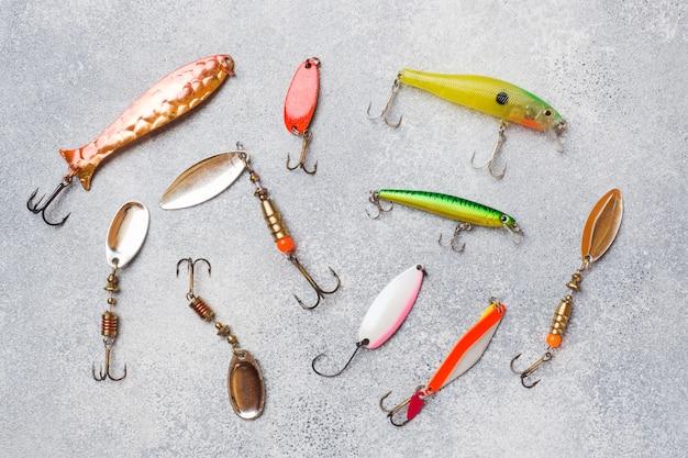 Vishaken en aas in een set voor het vangen van verschillende vissen op een grijze tafel met kopie ruimte. plat liggen