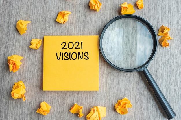 Visions-woorden op gele notitie met afgebrokkeld papier en vergrootglas