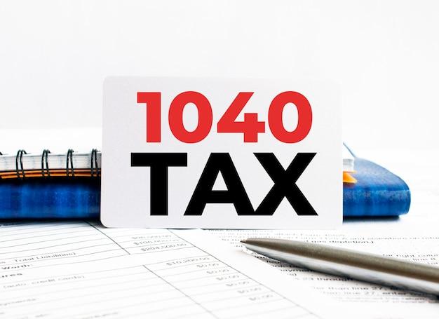 Visitekaartje met tekst 1040 tax liggend op blauwe notebook.