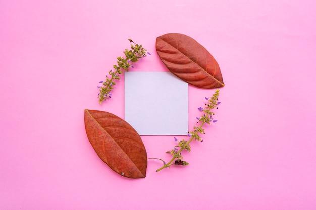 Visitekaartje op pastel roze achtergrond met gedroogde bloemen en bladeren decoratie. visitekaartje, witboek. papieren testmodellen. pastelkleurige achtergrond
