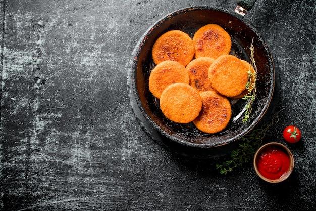 Viskoteletten in een oude pan met de tijm en tomatensaus in een kom. op zwarte rustieke achtergrond