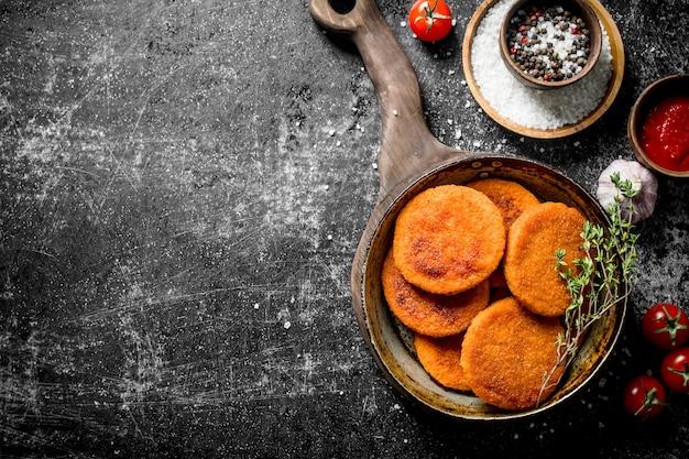 Viskoteletten met kruiden, tijm, knoflook en saus in kom. op zwarte rustieke achtergrond