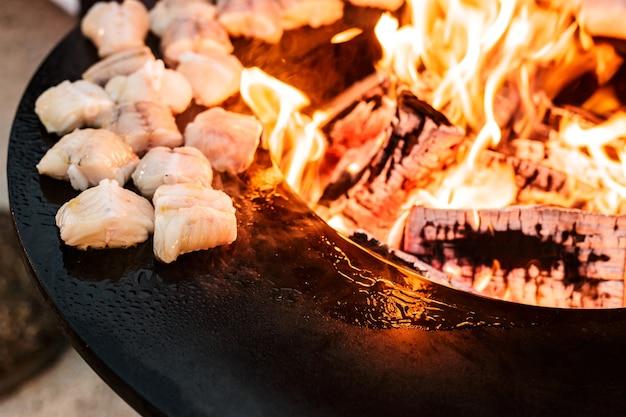 Vislapjes vlees zijn gegrilde close-up van stukjes vis ronde grill kom ronde braadpan met een vuur in de