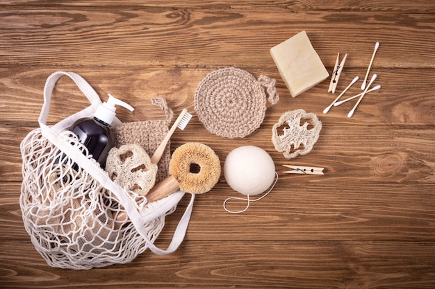 Visnet boodschappentas met ethische milieuvriendelijke schoonmaakproducten voor het huishouden: sisalborstel, natuurlijke luffa, bamboe tandenborstel, biologische zeep in fles, houten pinnen, knoppen, herbruikbare gezichtskussens, spons konjac
