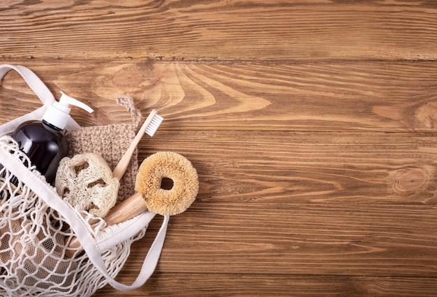 Visnet boodschappentas met ethische milieuvriendelijke schoonmaakset huishoudelijke producten: sisalborstel, natuurlijke luffa, bamboetandenborstel, biologische zeep in fles, houten pinnen. ruimte voor tekst