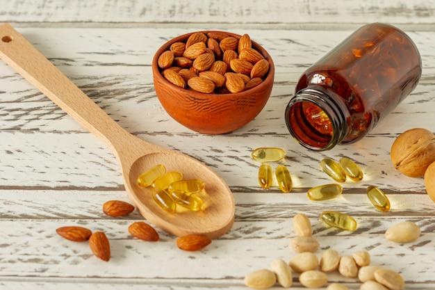 Visoliecapsules en assortiment van noten op houten achtergrond en textuur, vitamine d, omegasupplement, selectieve aandacht.
