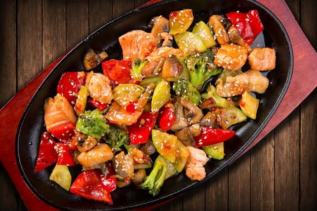 Vissalade met stukjes zalm, groenten, champignons en sesam, in een koekenpan op het bord