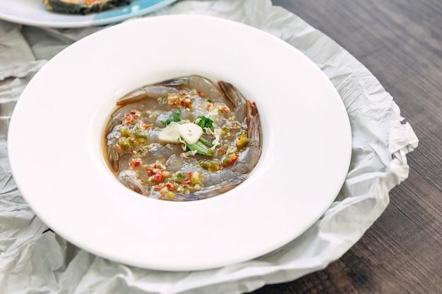 Vissaus-gefermenteerde rauwe garnalen met verse knoflook en chili.