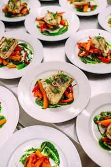 Visschotel met groenten voor catering. veel borden.