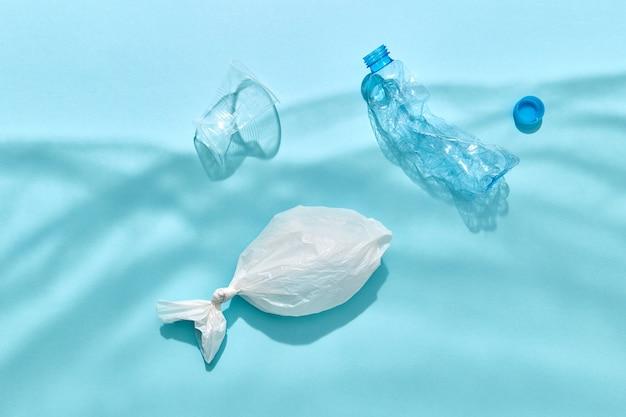 Vissen in plastic zak en plastic flessen drijven onder water uit schaduwen op een pastelblauwe muur, kopie ruimte. ecologisch probleem van vervuiling wereld oceaan.