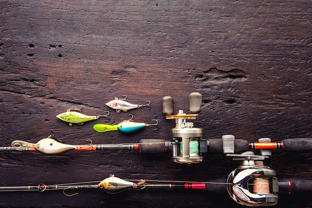 Vissen lokt, haken en accessoires op donkere houten achtergrond