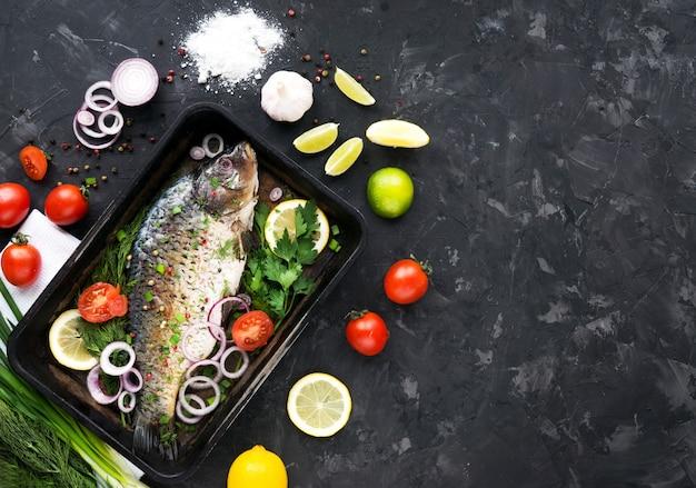 Vissen met kruiden op een donkere achtergrond. kookproces