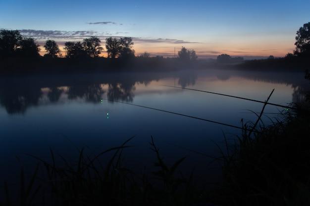 Vissen op mistig meer in de vroege ochtend net voor zonsopgang.