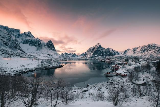 Vissend dorp in sneeuwberg met zonsonderganghemel bij kustlijn