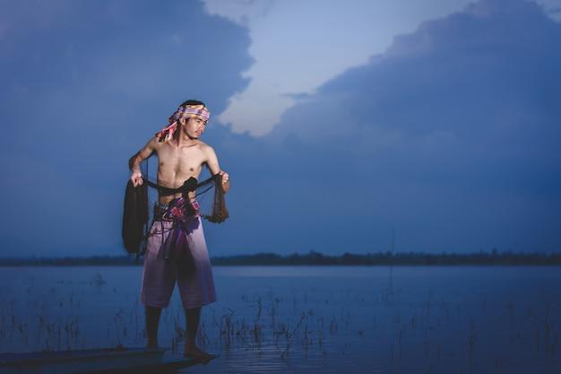 Vissende man gebruik gooien net om vis te vangen in het meer bij zonsondergang