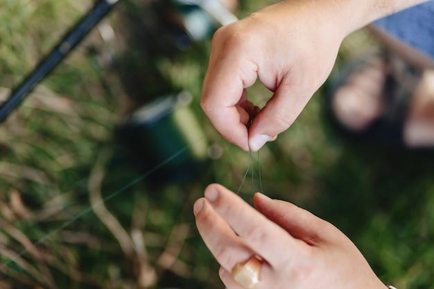 Visser bereidt snap voor op het vangen van karpers aan het meer in de zomer