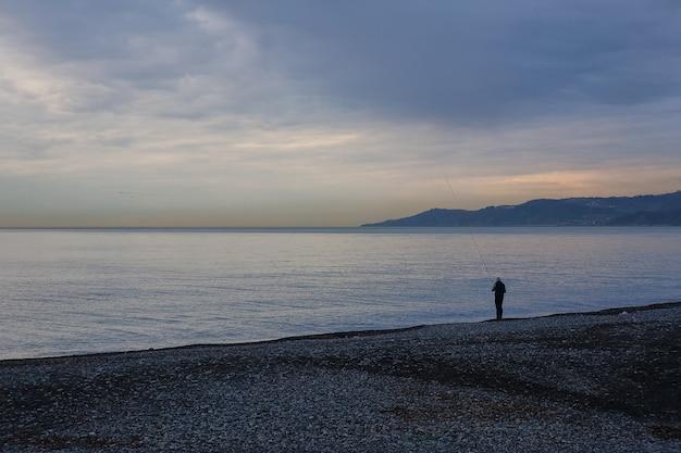 Visser bij zonsopgang door de zee