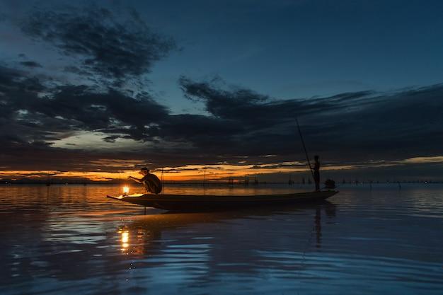 Visser die op boot vissen met zonsondergang vangt