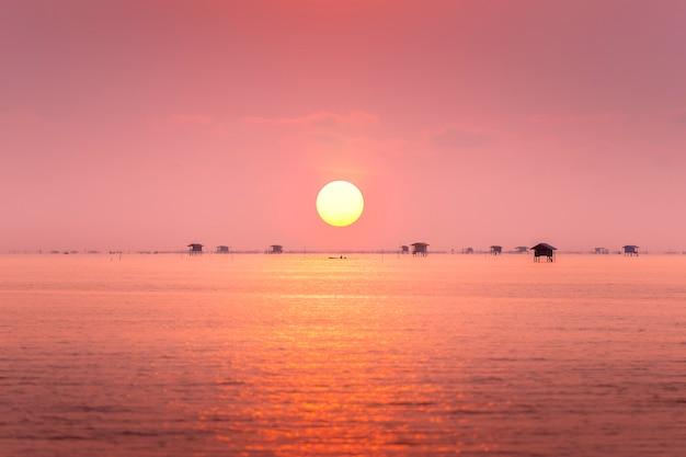 Visser en drijvend dorp in de oceaan bij zonsopgang