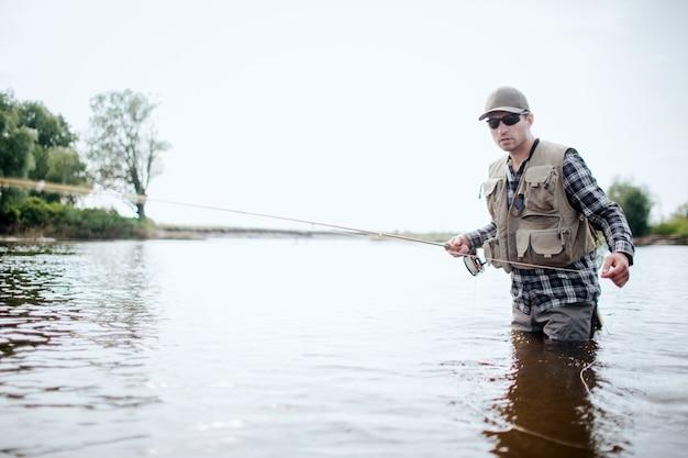 Visser in beschermende kleding loopt in water en vist. hij houdt de hengel in de ene hand en trekt de lepel met de andere hand naar rechts. man draagt een zonnebril. hij is geconcentreerd.