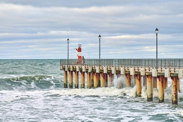 Visser in camouflage staande en vissen op pier met vuurtoren. zeegezicht.