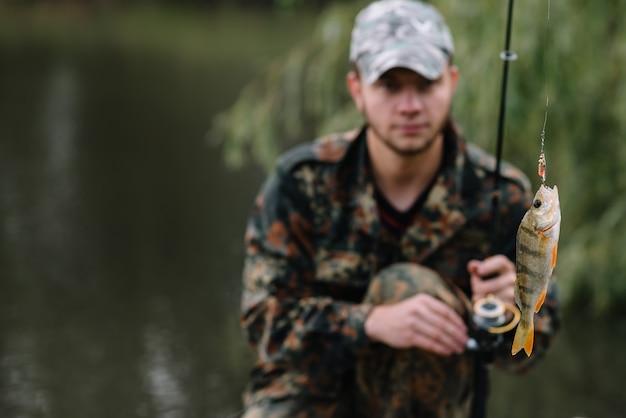 Visser in zijn hand met spinnen