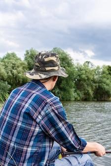 Visser man in de buurt van het water met een hengel op een rustige, kalme avond