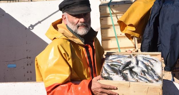Visser met een viskist in een vissersboot