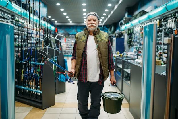 Visser met staaf en plastic emmer in visserijwinkel. mannelijke visser apparatuur en gereedschappen kopen voor het vangen en jagen van vissen, assortiment op showcase in winkel