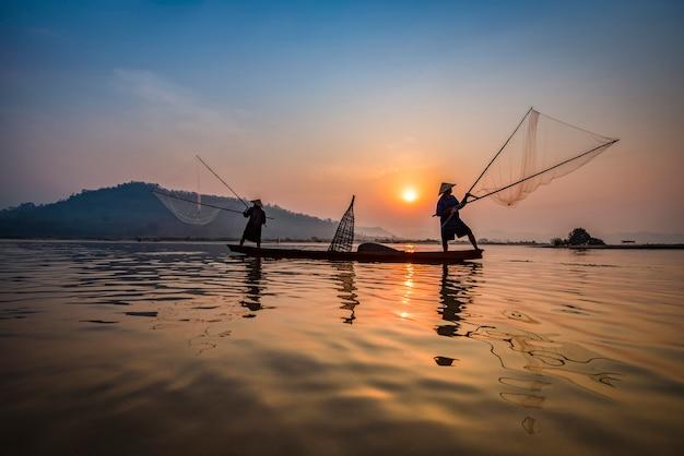 Visser op de zonsondergang van de bootrivier netto het gebruiken van azië op houten boot die netto zonsondergang of zonsopgang gieten