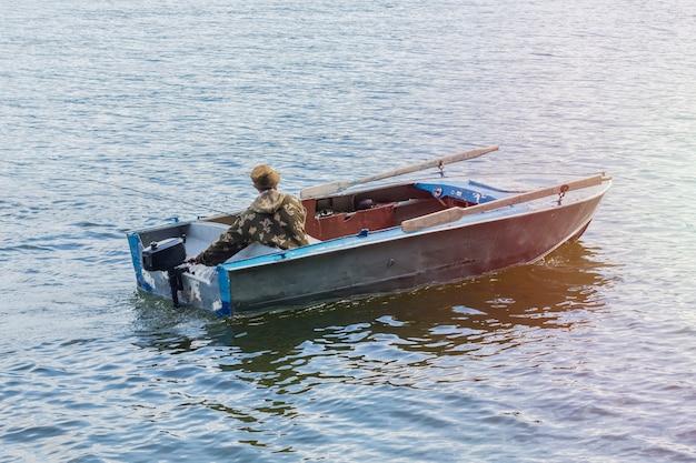 Visser op een oude motorboot, die vist naar het teletskoye-meer, republiek altai.