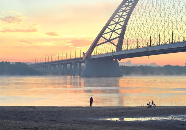 Visser op het strand. auto bugrinskij-brug over de grote siberische rivier ob in de ochtendmist