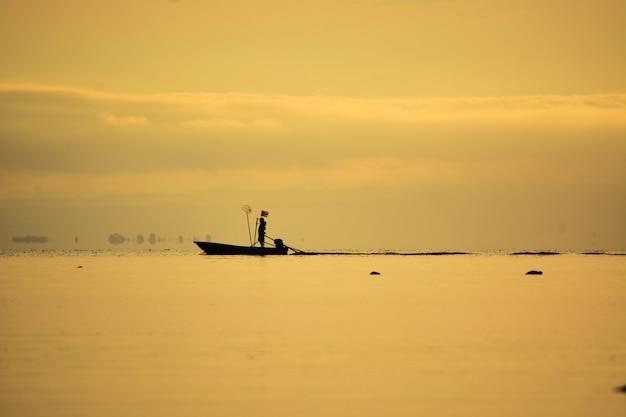 Visser staande op boot op zee