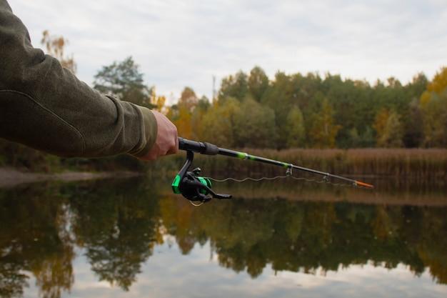 Visser vangt een vis op een hengel met een haspel op het meer
