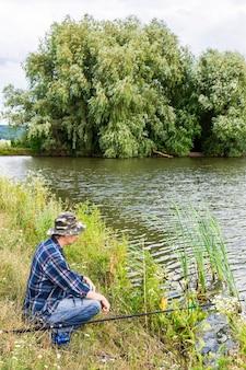 Visser vist op het meer, visser man aan het water met een hengel op een rustige rustige avond