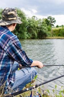 Visser vist op het meer, visser man in de buurt van het water met een hengel op een rustige rustige avond