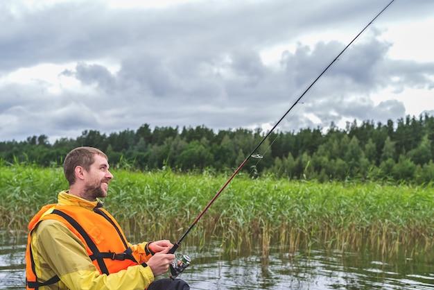 Visser zittend in een oude houten boot en vissen op een bewolkte dag.
