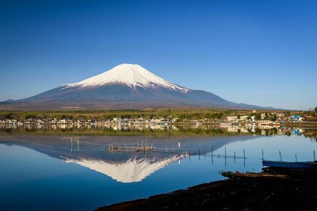 Visserijhulpmiddel op meer yamanaka met mount fuji of fujisan en stad met skyline reflectie tegen blauwe hemel, yamanashi, japan. 1 van 5 fujisan-meren. beroemde reisbestemming.