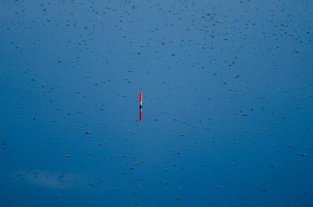 Visserijvlotter op blauwe watervijver