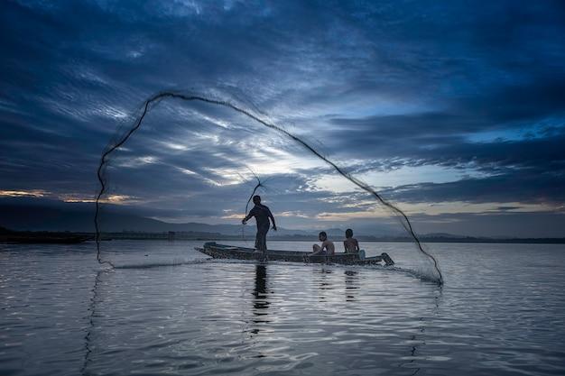 Vissers gieten gaat 's morgens vroeg vissen met houten boten, oude lantaarns en netten. concept fisherman's levensstijl.