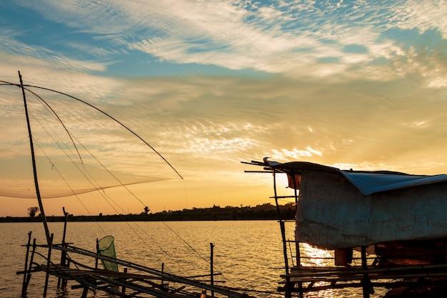 Vissers visserijhulpmiddelen in het meer bij zonsondergang
